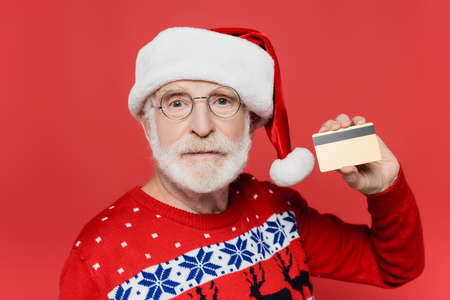 Senior man in sweater and santa hat showing credit card isolated on red Stock Photo