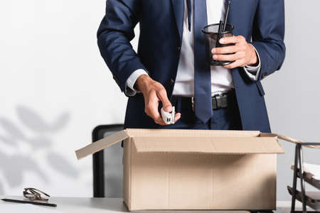 Cropped view of fired businessman holding stationery near carton box on table in office