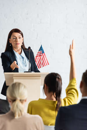 speaker pointing with hand at woman with raised hand in conference hall, blurred foreground