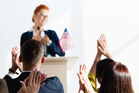 grateful speaker in front of applauding voters in conference room on blurred background