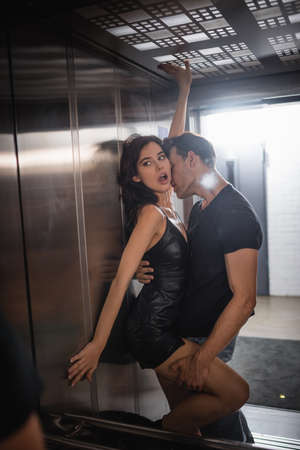 Passionate man embracing and holding leg of seductive woman with outstretched hands looking at mirror in elevator