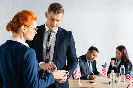 man pointing with finger near colleague while party members working on blurred background