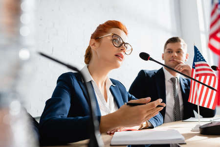 Thoughtful politician looking at female colleague speaking in microphone, while sitting in boardroom on blurred foreground