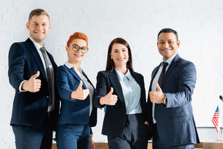 Smiling multicultural politicians with thumbs up looking at camera while standing in boardroom