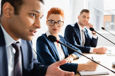Redhead female politician looking at indian colleague speaking in microphone during political party meeting in boardroom on blurred foreground