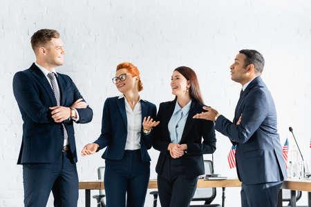 Happy interracial politicians gesturing while talking in boardroom