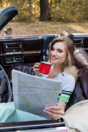 smiling woman holding coffee and looking at map in cabriolet on blurred foreground