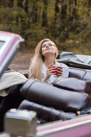 young woman relaxing while holding cup of coffee with closed eyes in vintage cabriolet on blurred foreground
