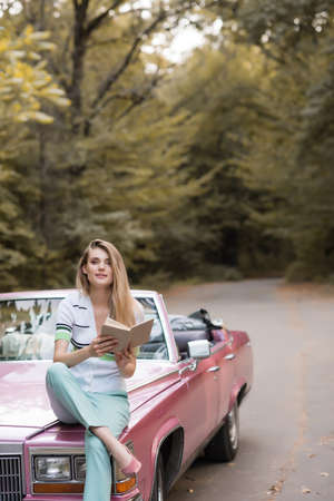 smiling woman looking at camera while sitting on hood of cabriolet and holding book