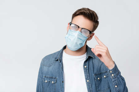 Young man in medical mask pointing with finger at misted eyeglasses isolated on gray