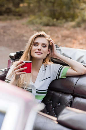 smiling woman touching head while holding cup of coffee and looking at camera in cabriolet on blurred foreground