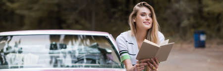 smiling woman sitting on car with book and looking away on blurred background, banner