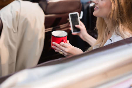 partial view of young woman holding smartphone with blank screen and cup of coffee on blurred foreground