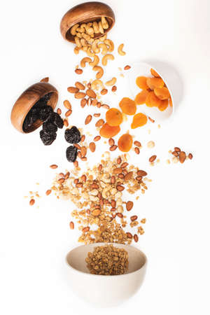 top view of delicious granola with nuts and dried fruits scattered from bowls isolated on white