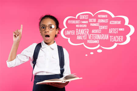 shocked african american schoolgirl with book showing idea gesture near thought bubble with greeting lettering on pink Zdjęcie Seryjne