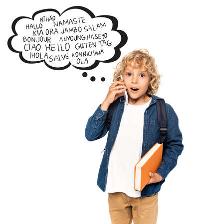shocked and blonde schoolboy holding book and talking on smartphone near speech bubble with greeting words on white