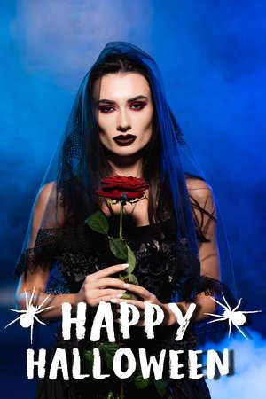 brunette bride in black dress and veil holding red rose near happy halloween lettering on blue