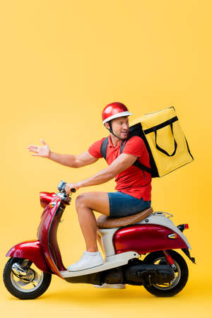 displeased delivery man with backpack gesturing while riding scooter on yellow Stok Fotoğraf