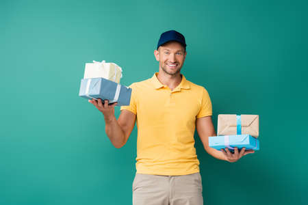 happy delivery man in cap holding wrapped presents on blue