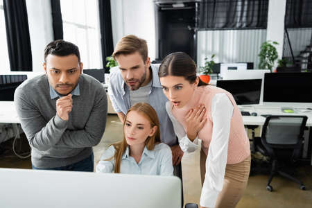 Excited multiethnic businesspeople looking at computer monitor on blurred foreground in office