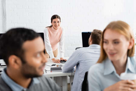Smiling businesswoman looking at colleague near devices in office