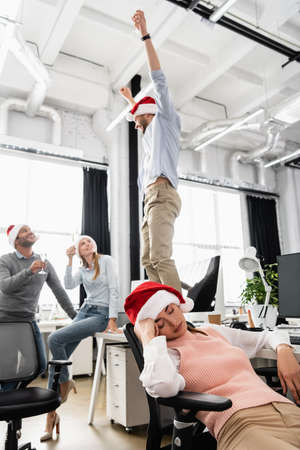 Businesswoman in santa hat sleeping near cheerful multiethnic colleagues on blurred background in office
