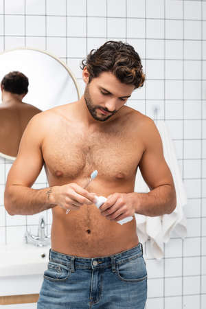 Shirtless man in jeans holding toothpaste and toothbrush in bathroom