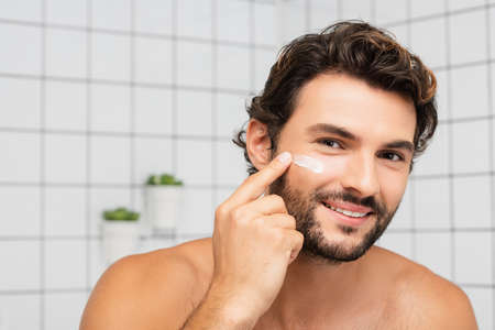 Smiling man applying cosmetic cream on face in bathroom