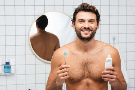 Cheerful shirtless man looking at camera while holding toothpaste and toothbrush in bathroom