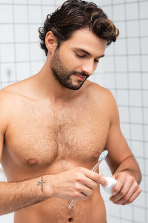 Shirtless man holding toothbrush and toothpaste in bathroom 版權商用圖片