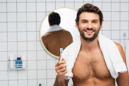 Smiling shirtless man with towel around neck holding toothbrush in bathroom