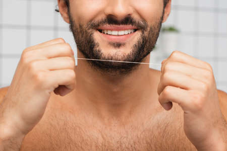 Cropped view of bearded man smiling while holding dental floss in bathroom