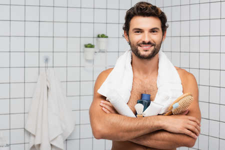 Smiling man with towel around neck holding comb, toothpaste with toothbrush and after shaving lotion in bathroom