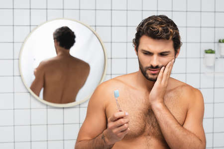 Shirtless man holding toothbrush while touching painful cheek in bathroom 版權商用圖片