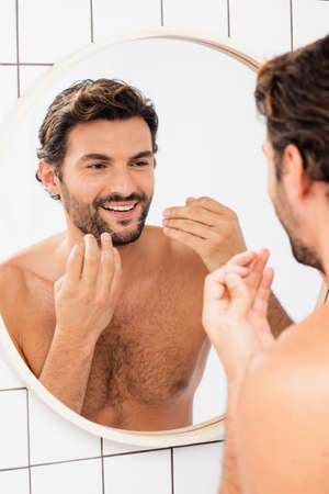 Shirtless man smiling while holding dental floss near mirror on blurred background