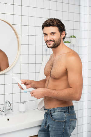 Shirtless man smiling at camera while holding toothpaste and toothbrush in bathroom 版權商用圖片