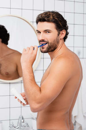 Shitless man looking at camera while brushing teeth and holding tube with toothpaste in bathroom