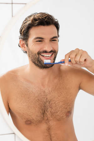 Shirtless man smiling at mirror while holding toothpaste and toothbrush in bathroom 版權商用圖片