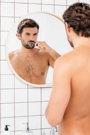 Barded and shirtless man looking at mirror while brushing teeth on blurred foreground in bathroom