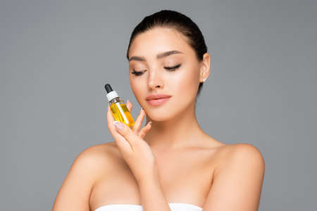 woman holding bottle with serum isolated on gray
