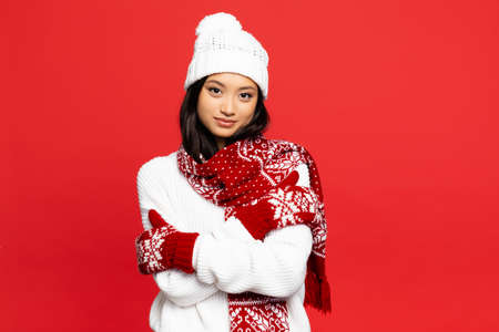cheerful asian woman in mittens, hat and scarf embracing herself isolated on red
