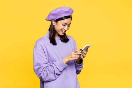 happy asian woman in beret looking at smartphone isolated on yellow Stockfoto