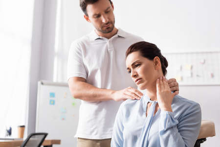 Massage therapist massaging painful neck of businesswoman with blurred office on background