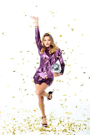 happy elegant woman in sequin dress with disco ball under falling confetti isolated on white