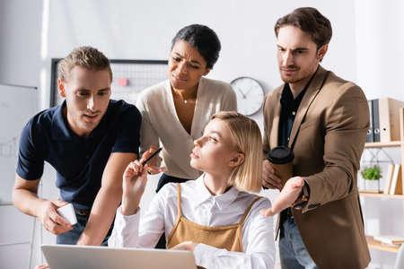 Blonde woman looking away while sitting at table with skeptical, multicultural office workers standing behind and looking at laptop at workplace