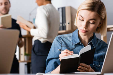 Blonde woman writing on notebook in office with blurred multicultural co-workers on background