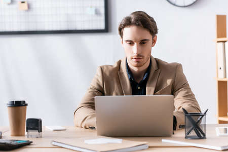Focused office worker looking at laptop, while sitting at desk with stationery in office on blurred background Foto de archivo