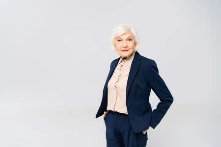 Senior woman looking at camera while standing with hands in pockets of pants isolated on gray Stock Photo