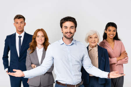 Cheerful businessman pointing with hands near multiethnic colleagues isolated on gray