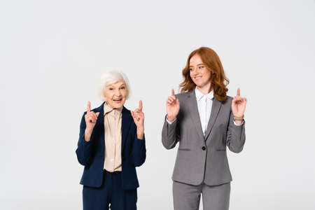 Smiling businesswomen pointing with fingers isolated on gray